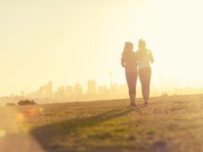 caregiver for inflammatory bowel disease, women walking/exercising in city park at sunset