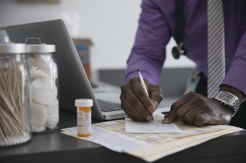 doctor writing prescription for anti-inflammatory drugs for IBD